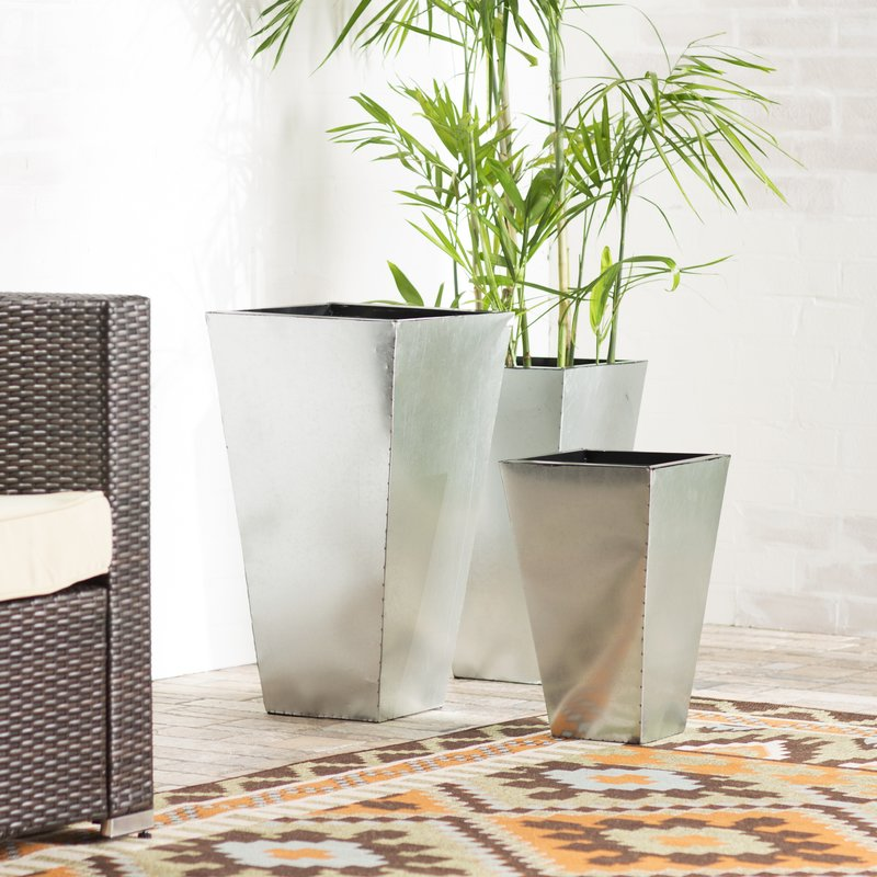Planters with raw edged metal in tapered geometric shapes