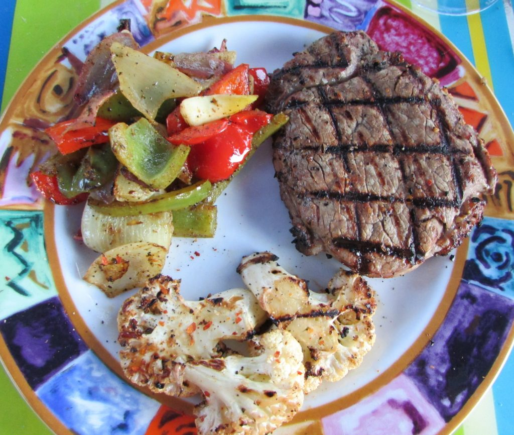 Grilled steak, onions and peppers, and grilled cauliflower