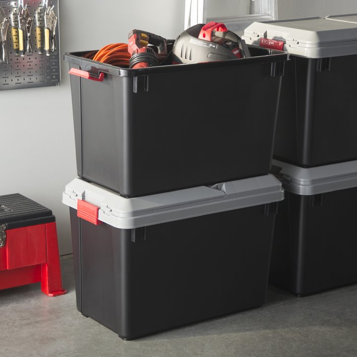 Heavy duty black storage bins on garage floor.