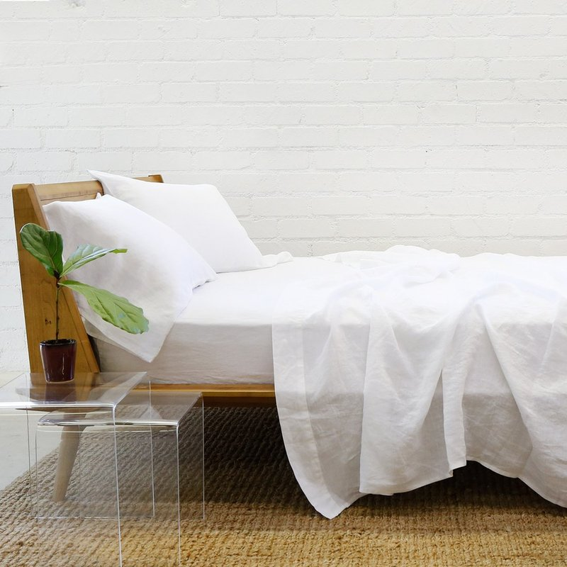 Wooden bed dressed with white linen bed sheets.