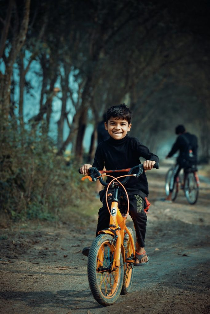 Happy Boy Riding His Bike on a Forest Path