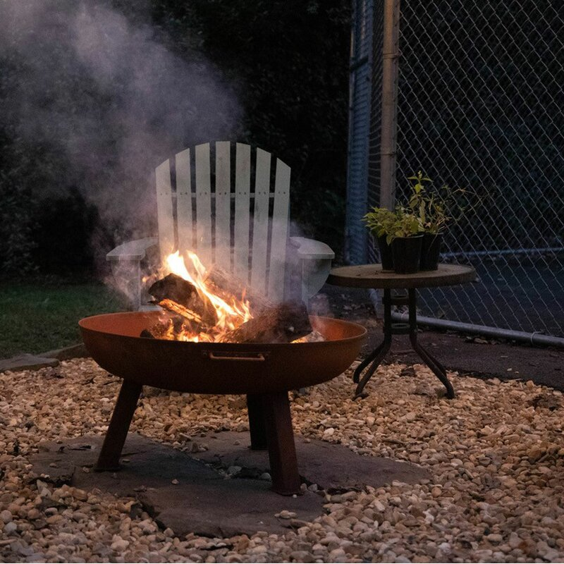 Open Bowl Cast Iron Wood Burning Fire Pit on Gravel and Natural Stones
